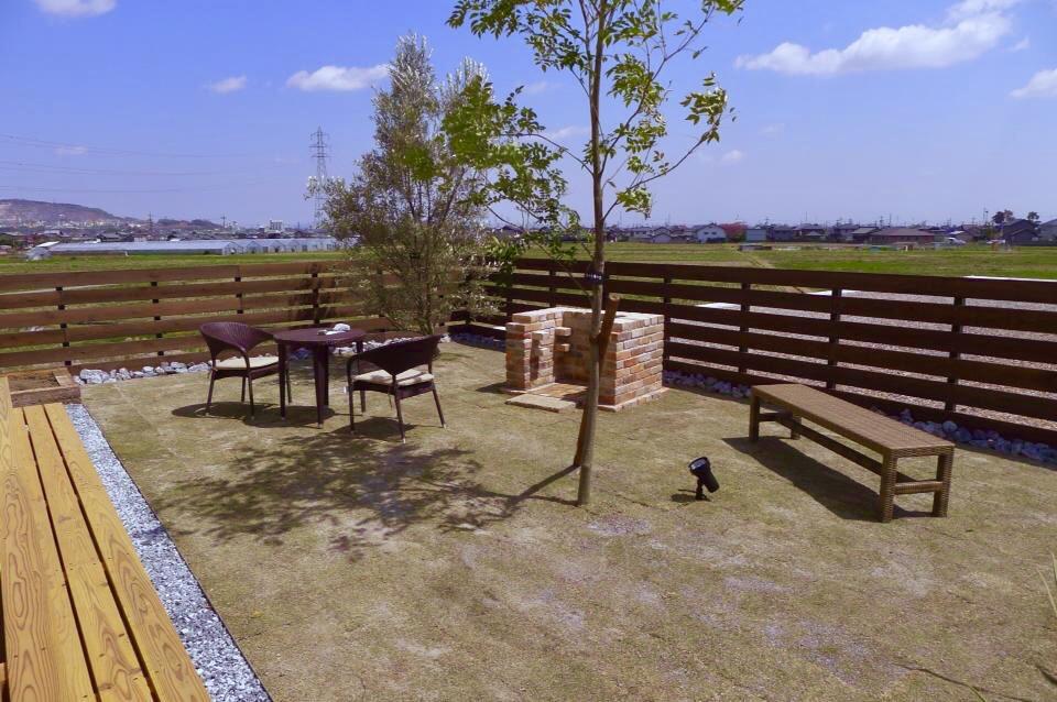 屋外用のテーブルやチェア、バーベキュー炉、ウッドデッキ、芝生と理想型なお庭に仕上がってます